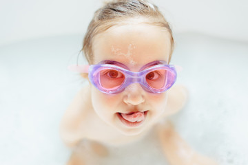 Cute young girl with swim goggle sticking out her tongue while sitting in a bathtub