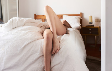 Woman with naked legs lying on bed with white linen
