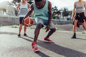 Young man playing basketball with group of friends