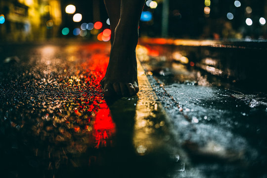 feet on wet road at night