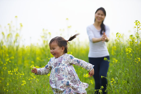 mother and little girl in the spring field