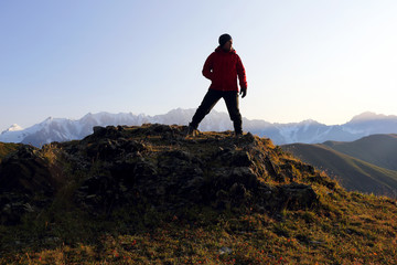 tourist stands on a hill in a mountainous area in Georgia.