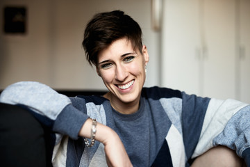 Young androgynous woman with toothy smile looking at camera