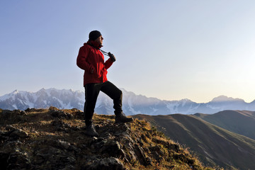 tourist with binoculars looking in a mountainous