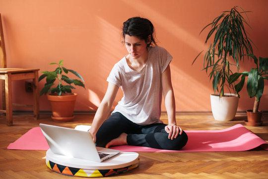 Woman having home yoga class