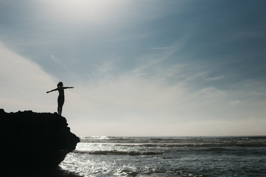 Woman feeling uplifted and empowered on a rock above the ocean