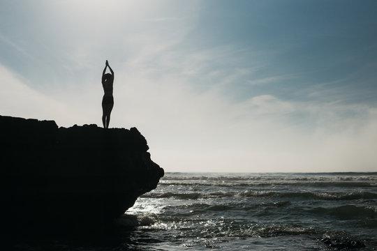Young female yogi balancing on a rock above the crashing waves