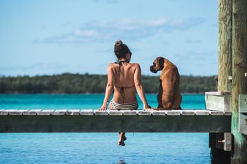 Gorgeous young woman in Bikini sittin gon Dock with Boxer puppy