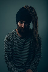 Man with dreadlocks sticking out of a wool hat. Straight on.