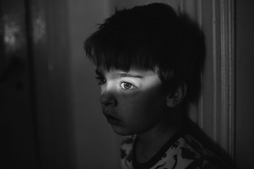 Black and white of boy in dark room with a bright strip of light across his eyes.