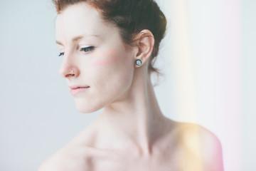 Stylized studio beauty shot of topless woman wearing facepaint