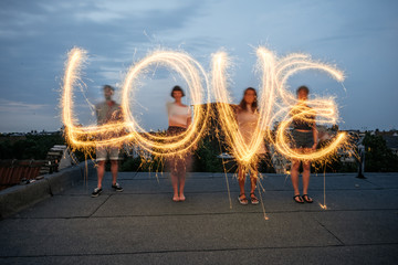 Four people writing the word 'love' with sparklers.
