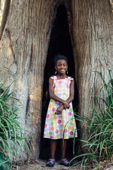 African American girl in a tree hollow