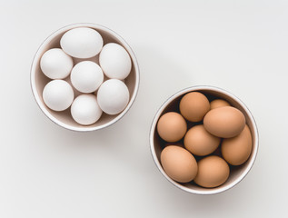 Bowls of white and brown eggs
