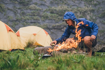 outdoorsman tending a fire in a camp in the mountains