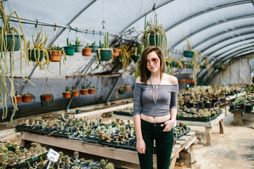 Portrait of a young woman in a cactus greenhouse