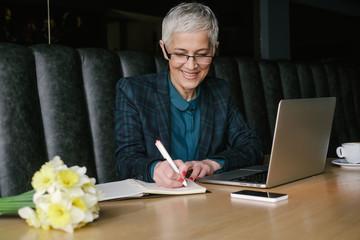 Smiling Senior Businesswoman Writing Notes while Working