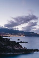 Volcanic coastline and lights of Santa Cruz at twilight. La Palma, Canary Islands.