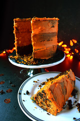 sliced Halloween cake with orange frosting on dark background