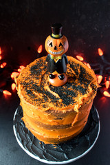 Halloween cake with orange frosting on dark background