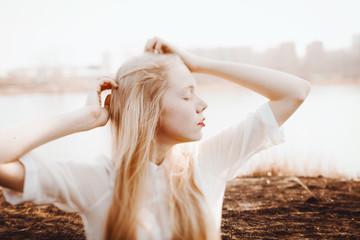Young blond girl enjoying spring wind