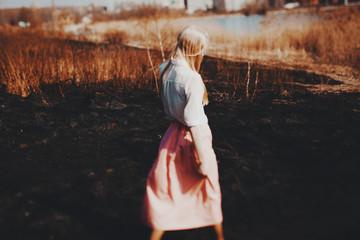 Blonde girl walks on the burned field