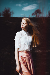 Young blonde woman stay is burned field white shirt and pink skirt