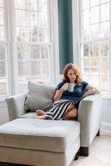 Beautiful woman sitting in a big chair reading a magazine and drinking coffee