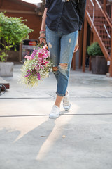 Woman wearing jeans and holding a bouquet of flowers