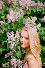 Portrait of a young woman among lilac in blossom
