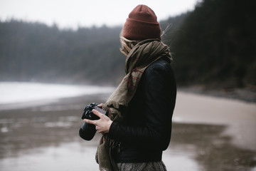 young woman taking photos at beach on cloudy day