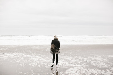 young woman walking by ocean on overcast day with camera