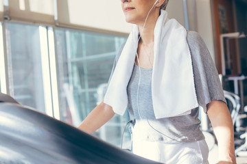 Woman Listening to Music While Walking on a Treadmill