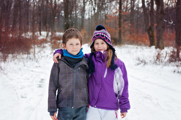 Winter portrait of two friends in the snowy woods standing next to each other