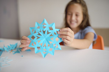 Making of snowflakes from blue paper.