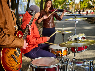 Festival music band. Hands playing on percussion instruments in city park. Drums with sticks closeup. Body part of male musicians. Autumn street musician makes money for a living.