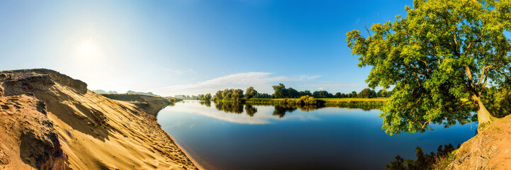 Wall Mural - Summer landscape with river, sun and blue sky