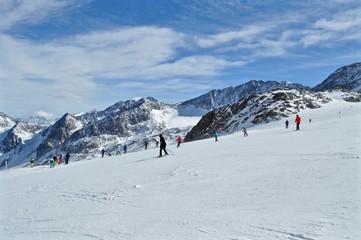Skifahren auf der Piste vom Stubaier Gletscher, Tirol, in Österreich. Im Hintergrund verschneite Tiroler Berge und Wildpfaff
