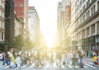 Crowds of colorful diverse people walking across a busy intersection in New York City with the light of the sun glowing in the background