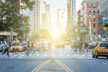 Photo sur Plexiglas Lieux connus d Amérique People crossing the busy intersection between traffic on 3rd Avenue and 10th Street in Manhattan in New York City with the glow of sun light in the background