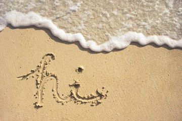 Cursive writing in the sand with a wave coming in on the shore