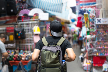 Young Asian man traveler with backpack walking market street vacation, tourism concept traveling on holidays in Hong Kong