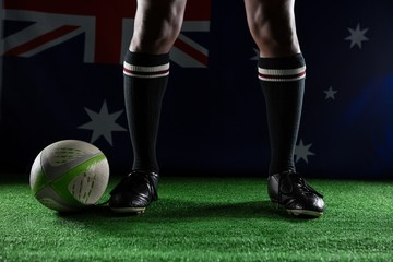 Low section of rugby player standing against Australian flag