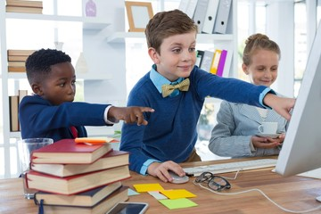 Kids as business executives discussing over desktop pc
