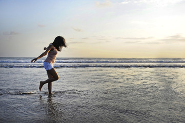 young happy and excited Asian woman having fun enjoying playful and free at sunset beach in tourism vacation