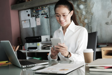 Young businesswoman using smart phone while working at her office desk background, business people and communication concept, office lifestyle