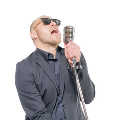 A man in a gray jacket, bow tie and sunglasses singing with a microphone in his hand. Isolated