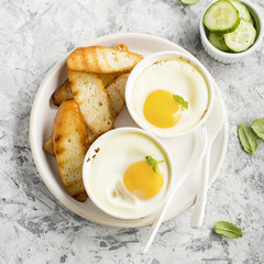 Breakfast for two. Eggs baked in the oven in ceramic portioned forms with toasted bread and slices of fresh cucumber. Top View.