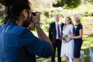 Photographer taking photo of bride and her parents