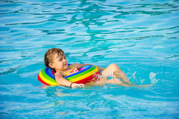 The child is bathing in the pool at the resort. Selective focus.